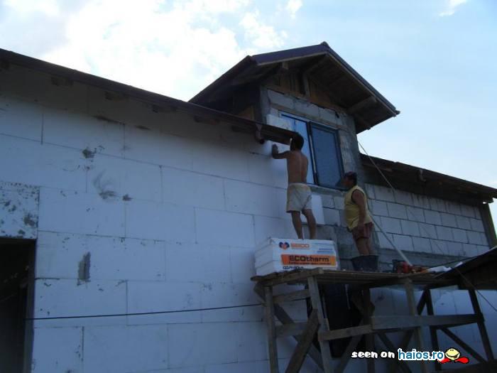doi_muncitori_lucreaza_la_izolarea_termica_fonica_zid_casa_constructie.jpg